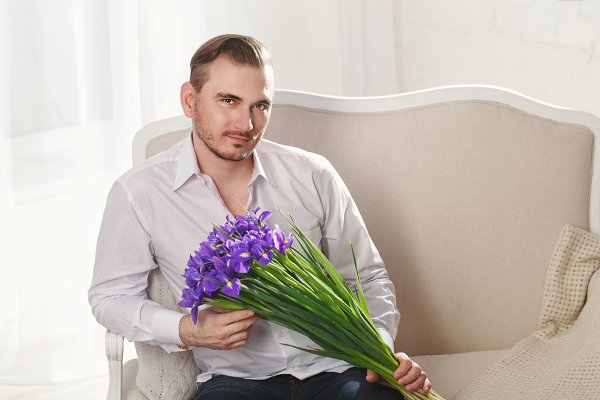 Male model with bouquet of flowers.