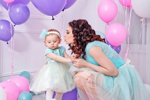 Mother kisses daughter. Balloons.