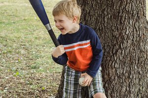 Boy with Bat and Ball Laughing