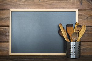 Wooden background with a chalkboard and cooking utensils