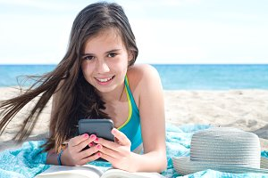 girl with smartphone on beach