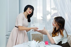 Girl gives gift friend. Tea party