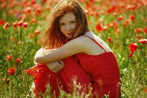red haired girl in poppy field