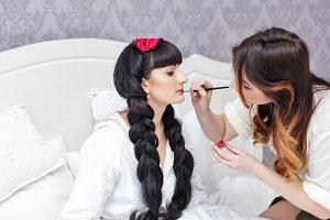 Makeup artist doing make-up bride.