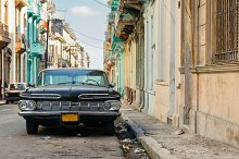 Panoramic view of Havana street with crumbling buildings and old classic car