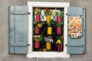 Three colourful windows with decorative flover pots.