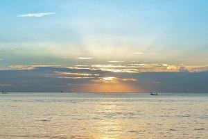 Sunset on the beach with beautiful sky in Thailand, Phuket. Boats on horizon.
