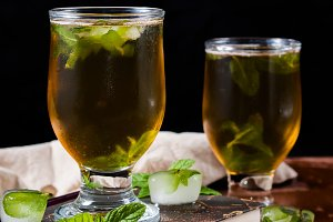 Cold tea with ice and mint leaves on dark background