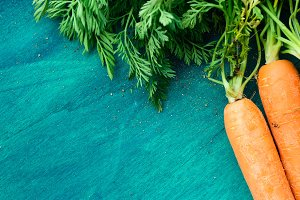 Fresh carrots on dark green