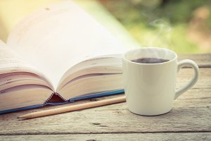 Cup of coffee with notebook on wood.