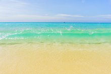 Sea beach with waves, blue sky and white sand. Beautiful wavy sea. Empty sea shore.