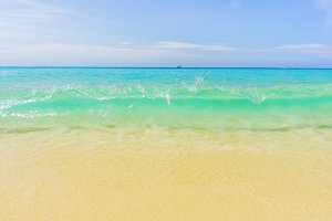 Sea beach with waves, blue sky and white sand. Beautiful wavy sea. Empty sea shore.