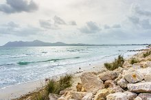 Big rocks on a seashore. Wavy sea near rocky beach.
