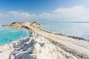 View of Dead Sea coastline. Road into the dead sea.