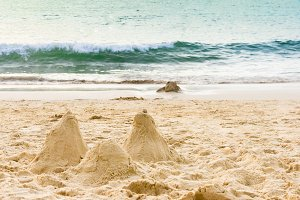 Sand castle on the beach. Sand castle model near wavy sea. Sea castle made on beautiful white sand beach.