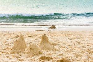 Sand castle on the beach. Sand castle model near wavy sea. Sea castle made on beautiful white sand beach.
