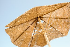 Broken parasol on the sky background