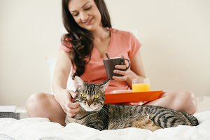 Woman to caress her cat in bedroom.