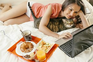 Woman working with laptop in bedroom
