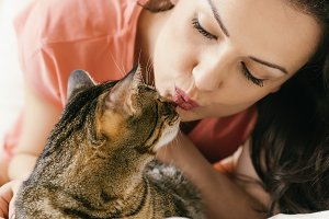 Woman kissing her cat in bedroom.