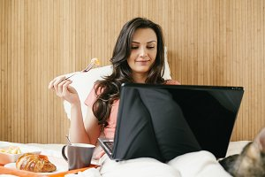 Woman having breakfast in bedroom
