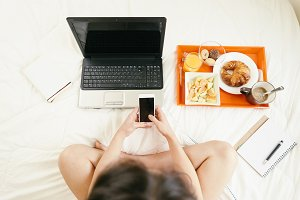 Woman usin mobile in bedroom
