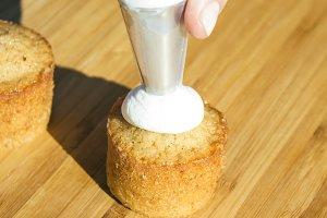 Pastry bag putting cream on cupcake