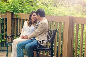 Expecting couple sitting on bench
