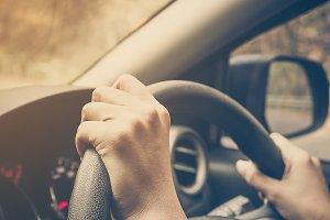 Hands 's driver on steering wheel.