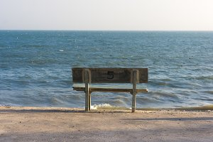 Comfortable bench near the sea with text five on back.