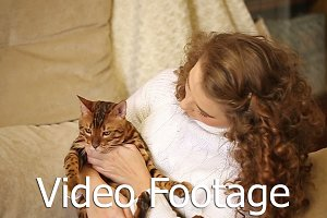 Girl playing with Bengal cat