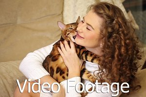 Girl playing and biting Bengal cat