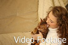 Girl hugs and bites ear Bengal cat