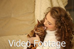 Girl hugs and bites ear Bengal cat