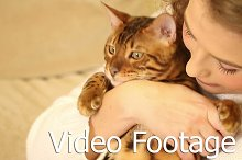 Girl hugging and playing with cat