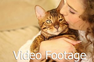 Girl embraces and kisses cat