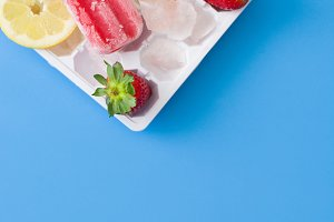 Strawberry popsicle. Blue background