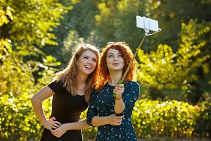 Two girls make selfie and smile.