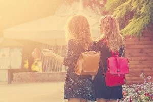Girlfriends walking through park.