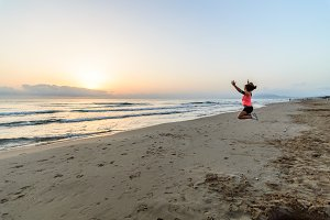 Girl jumping on the beach at dawn