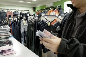 Man pays money by cash in the clothing store shop