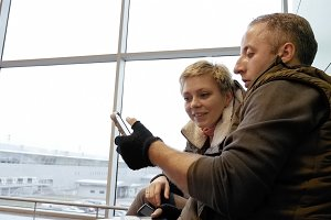 Happy couple or family looking at the smartphone