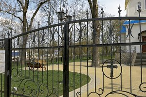 Metal fence and gate with cross of the churchyard