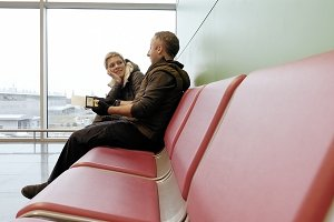 Couple waiting at airport terminal with tickets