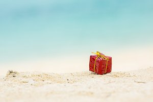 Christmas gift box on sand beach