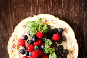 blueberries and raspberries on a plate ventazhnoy dark wood background