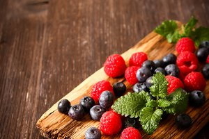 blueberries and raspberries on a wooden board background wood dark