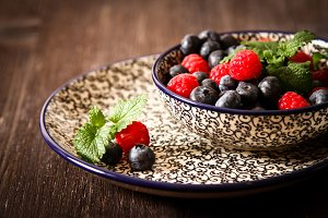 blueberries and raspberries on a plate with  black background pattern dark wood