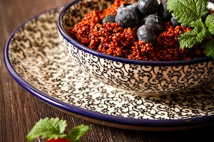 Quinoa blueberries and raspberries on a plate with black background pattern dark wood