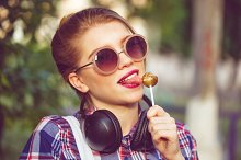 Hipster girl licking lollipop